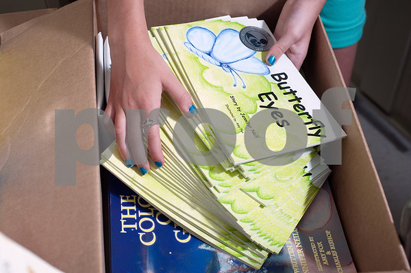 photo by Sarah A. Miller/Tyler Morning Telegraph  Abigail Price, 12, of Tyler, is pictured at the Literacy Council of Tyler office Thursday with some of the 2,000 books she donated to them.