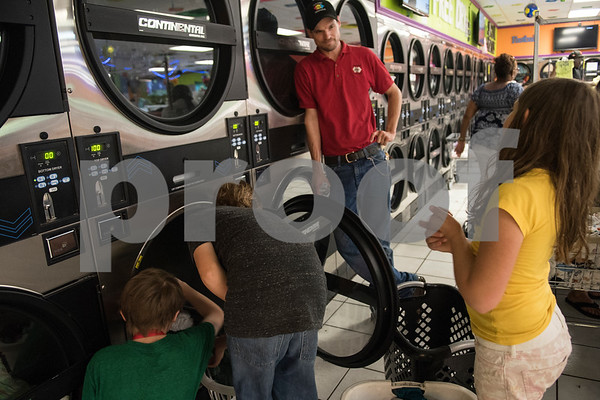 Kaleb, 10, Avrey 11, and Allyson, 8, help their father Christopher Skelton, 38, of Tyler, with laundry at Express Lavanderia June 6, 2016. It was the last night the family had to leave their home for laundry. The family moved into a Habitat for Humanity home with their own laundry room two days later.  (Sarah A. Miller/Tyler Morning Telegraph)