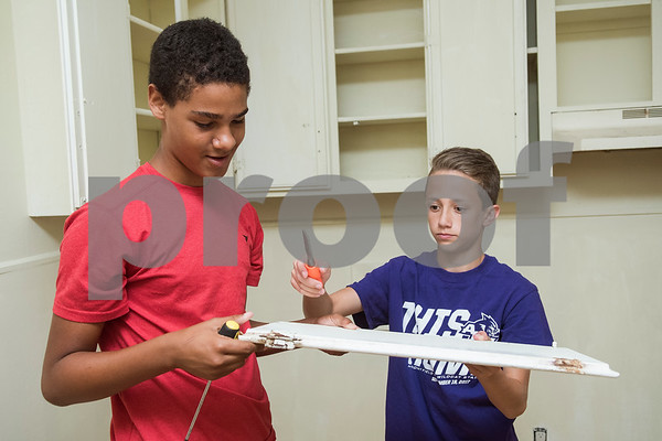 Jake Hosch, 14, and Dylan Dossey, 14, take hinges off of a kitchen cabinet door as they help remodel a PATH home as part of Middle School Mission Effort on Tuesday June 19, 2018. Middle School Mission Effort is a service event for middle school students from Glenwood Church of Christ in Tyler and Shiloh Road Church of Christ to learn basic service skills such as painting a house.   (Sarah A. Miller/Tyler Morning Telegraph)