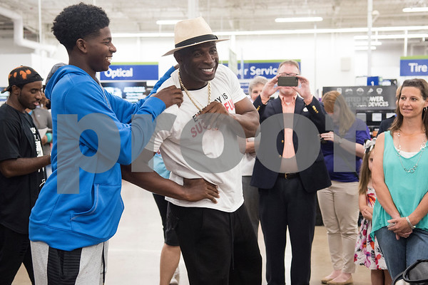 Shedeura Sanders, 15, jokes with his dad, Pro Football Hall of Famer Deion Sanders, before they participated in a shopping spree at Sam's Club in Tyler Tuesday June 20, 2017. The goal of the event was to collect up to $10,000 in merchandise in two minutes or less to provide relief to the victims of the Canton area tornadoes April 29, 2017.  (Sarah A. Miller/Tyler Morning Telegraph)