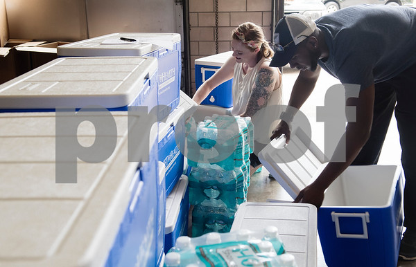 Nora Schreiber, the founder of The Worthy Ones, a Tyler nonprofit, and Cameron Royall fill up coolers with cold water bottles to be placed at 30 of the most heavily used bus stops in Tyler Tuesday June 20, 2017.  (Sarah A. Miller/Tyler Morning Telegraph)