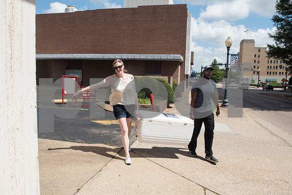 Nora Schreiber, the founder of The Worthy Ones, a Tyler nonprofit, and Cameron Royall deliver a cooler filled with cold bottled water to a bus stop in downtown Tyler Tuesday June 20, 2017.  (Sarah A. Miller/Tyler Morning Telegraph)