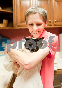 photo by Sarah A. Miller/Tyler Morning Telegraph  Tyler resident Mary Ann Clifford holds Daisy Mae in a towel after giving her a bath at her home Monday. Clifford is the author of new book Reflections of a Cat Whisperer. The autobiography provides information on the many facets of felines, inspirational and humorous stories about Clifford's cat encounters, as well as advice on how she handled cats with physical and emotional disabilities.