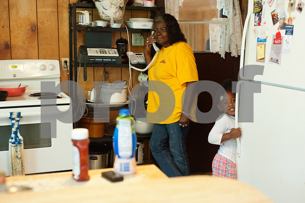 photo by Sarah A. Miller/Tyler Morning Telegraph  Jazmine McCin, 3, looks through the refrigerator for her favorite snacks while her great great grandmother Polly Jackson talks to her grandson Stepheon Jackson, 28, on the phone Thursday May 29, 2014. Jackson, 76, has raised her children, grand children, great grandchildren and great great grandchild at her Winona home.