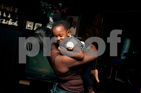 photo by Sarah A. Miller   Pictured April 8, 2013, Khamila Bradford, 15, holds her daughter Jazmine McCin, 2, after coming home from school. Bradford and her brother Keveonte, 13, are being raised by their great grandmother Polly Jackson, 75, in Winona.