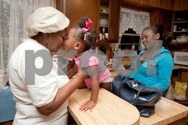 photo by Sarah A. Miller/Tyler Morning Telegraph   Pictured March 27, 2013, Jazmine McCin, 3, kisses her great great grandmother Polly Jackson, 75, while Jackson's great granddaughter, also McCin's mother, Khamila Bradford, 15, waits to leave for school. Jackson is raising several generations of family members in her Winona home as well as caring for her husband Ernest, 74.