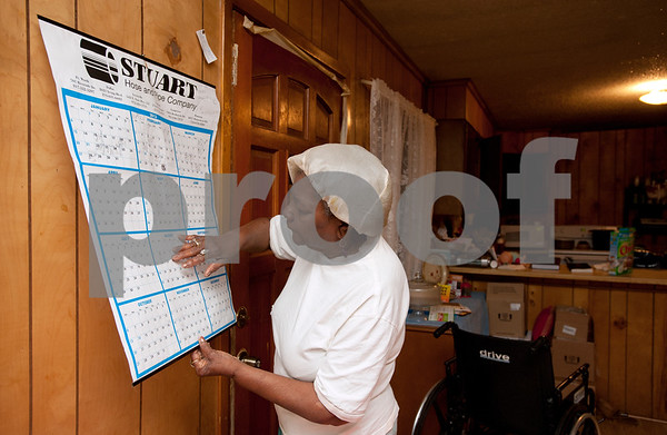 photo by Sarah A. Miller/Tyler Morning Telegraph   Pictured March 27, 2013, Polly Jackson, 75, checks her calendar to see the dates of upcoming doctor's appointments for her great grandson Keveonte Bradford, 13, who has cerebral palsy. Bradford, his sister Khamila Bradford, 15, and Khamila Bradford's daughter Jazmine McCin, 2, live with and are being raised by Mrs. Jackson.
