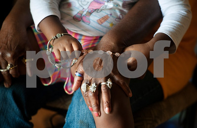 photo by Sarah A. Miller/Tyler Morning Telegraph  Jazmine McCin, 3, plays with her great great grandmother Polly Jackson's jewelry as she sits on her lap Thursday May 29, 2014. Jackson, 76, is head of her Winona home raising multiple generations of family members and caring for her husband Ernest, 75.