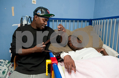 photo by Sarah A. Miller/Tyler Morning Telegraph    Pictured March 27, 2013, Stepheon Jackson removes a restraining strap from his relative Keveonte Bradford's, 13, arm so he can help him get out of bed. Bradford's arm is restrained because he has a bad habit of hitting himself to the point that he now has a glass eye from hurting himself. Jackson and Bradford have special bond because Jackson also has one glass eye from accident. Stepheon Jackson is Polly Jackson's grandson. He lives closeby and is a big help in caring for Keveonte and Polly's husband Ernest.
