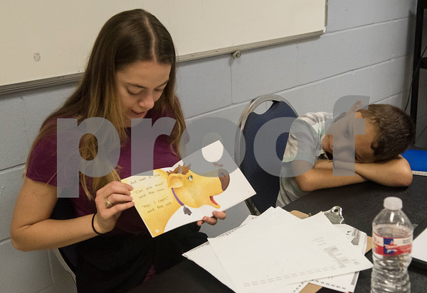 Nicole Hoffman reads to Joseph Lopez, 6, during a Read Across America summer reading program held at the Glass Recreation Center. The program aims to strengthen students' reading skills before they head back to school in the fall.  (Sarah A. Miller/Tyler Morning Telegraph)