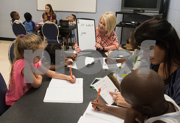 Christy Turner, center, works with children on their spelling during a Read Across America summer reading program held at the Glass Recreation Center. The program aims to strengthen students' reading skills before they head back to school in the fall.  (Sarah A. Miller/Tyler Morning Telegraph)
