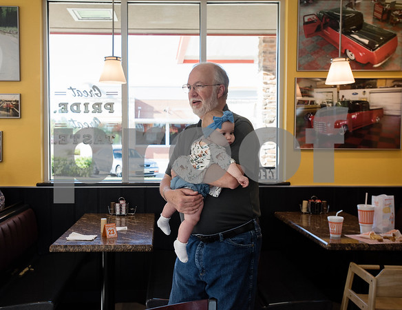 Randy White holds William White's baby sister Eleanor during a party hosted by Whataburger at Whataburger #1107 in Tyler on Tuesday June 26, 2018. William has autism, and going to Whataburger is one of his favorite things. Whataburger found out about his love for their restaurant and held a party for him.  (Sarah A. Miller/Tyler Morning Telegraph)