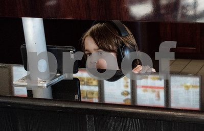 William White, 6, watches a video on a smartphone he balanced under a television screen at Whataburger #1107 in Tyler on Tuesday June 26, 2018. The store held a party for William who has autism and loves his daily trip to Whataburger with his family.  (Sarah A. Miller/Tyler Morning Telegraph)