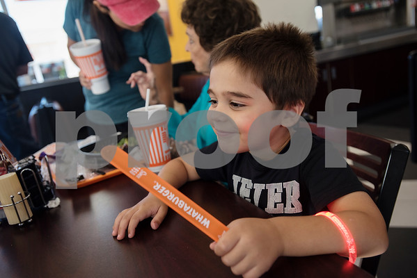 William White's cousin Levi Smoker, 3, wears one Whataburger bracelet and holds another in his hand during a party hosted by Whataburger at Whataburger #1107 in Tyler on Tuesday June 26, 2018. William has autism, and going to Whataburger is one of his favorite things. Whataburger found out about his love for their restaurant and held a party for him.  (Sarah A. Miller/Tyler Morning Telegraph)