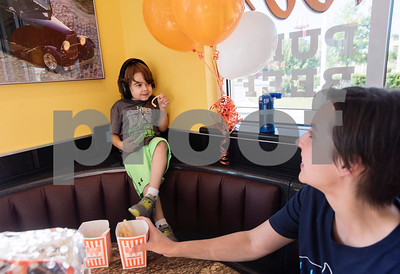 Natalie White sits with their son William White 6, during a special party held for William at Whataburger #1107 in Tyler on Tuesday June 26, 2018. William has autism, and going to Whataburger to eat French fries is part of his daily routine. He wore headphones to block out excess noise because he is sensitive to loud sounds.  (Sarah A. Miller/Tyler Morning Telegraph)