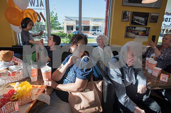 William White, 6, interacts with his mom Natalie White, at left, while relatives and friends enjoy free meals during a special party held for William at Whataburger #1107 in Tyler on Tuesday June 26, 2018. William has autism, and going to Whataburger to eat French fries is part of his daily routine. He wore headphones to block out excess noise because he is sensitive to loud sounds.  (Sarah A. Miller/Tyler Morning Telegraph)