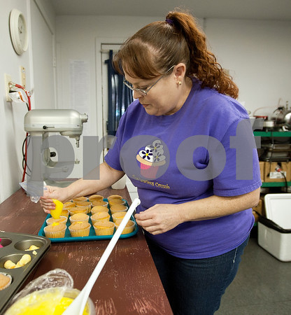 """photo by Sarah A. Miller/Tyler Morning Telegraph  Owner Dawn Trammell puts filling inside lemon cream cupcakes Wednesday at Mineola bakery The Luscious Crumb. The bakery which is known for its 100 flavors of cupcakes, will be featured on an upcoming episode of the Food Network's television show """"Cupcake Wars."""" A watch party for the episode will be held Sunday June 30 at 6 p.m. at the Lake County Playhouse/Select Theater in downtown Mineola."""