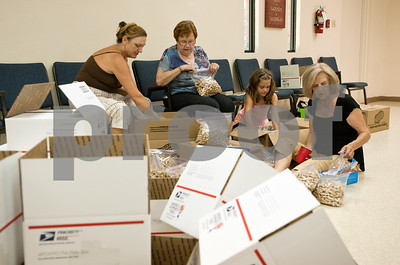 photo by Sarah A. Miller/Tyler Morning Telegraph  Nancy Nunez of Longview, Anne DeLaet, Eva Conley, 7, of Tyler, Shirley Snowden of Lindale divide peanuts into snack bags to be mailed to soldiers through the Adopt-A-Box program Monday June 10.