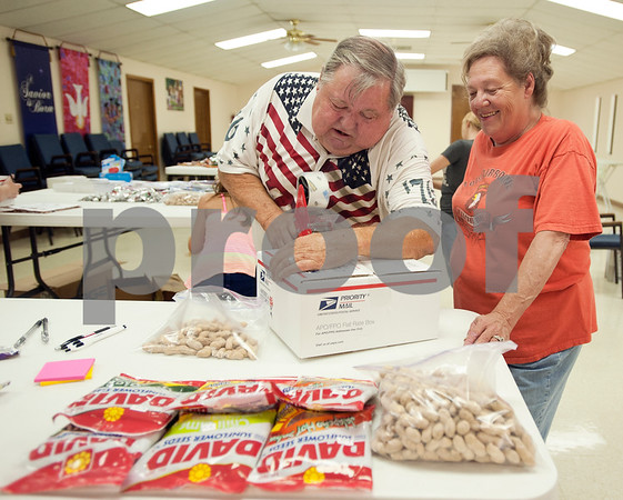 photo by Sarah A. Miller/Tyler Morning Telegraph  Walter Morman of Tyler helps his wife Polly Morman with taping closed boxes that will be sent to soldiers overseas. The Adopt-A-Box program headed by Polly Morman meets several times a year to gather donations and put together care packages of snack foods and hygiene items for soldiers.