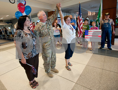 photo by Sarah A. Miller/Tyler Morning Telegraph  Anne DeLaet of Welcome Home Soldiers, right, holds her hand up to celebrate the safe return of Tyler resident Staff Sergeant Thomas Paul, US Army National Guard Thursday June 20 at the Tyler Pounds Regional Airport.  SSGT Paul returned from serving in Kandahar, Afghanistan since Nov, 2012 as a Combat Medic training the Afghanis. Also pictured is Paul's wife Mary Paul.