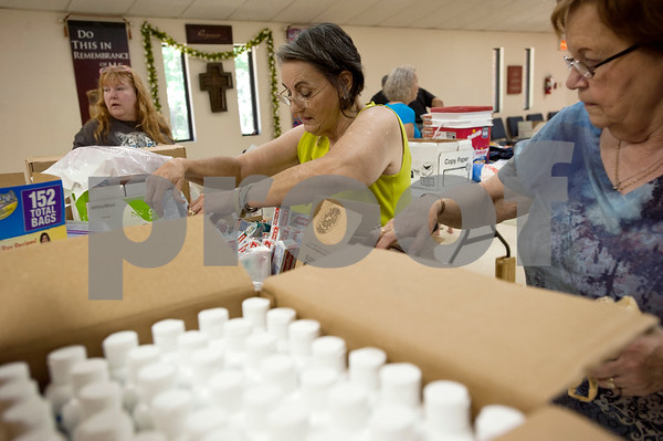 photo by Sarah A. Miller/Tyler Morning Telegraph  Angel Johnson of Henderson, left, Betty Dodson of Longview, center, and Anne DeLaet volunteer their time packing boxes Monday June 10 for Adopt-A-Box. Adopt-A-Box is a grassroots organization that collects and mails food items and hygiene items to American soldiers overseas.