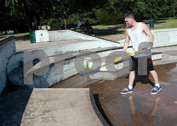 photo by Sarah A. Miller  Ben Jordan, 19, uses a squeegee to mop up a flooded section of Noble E. Young Skatepark after a brief downpour June 9, 2015. The East Texas Skatepark Association hopes to make improvements to Tyler's skatepark.