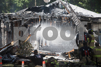 Smith County ESD2 fire fighters work putting out a structure fire in the 16,000 block of Big Oak Bay Road in New Chapel Hill. No one was injured in the fire.  (Sarah A. Miller/Tyler Morning Telegraph)