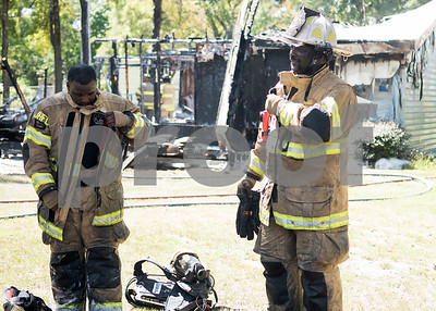 Smith County ESD2 fire fighters Travis Johnson and Kelcey Trotty work at a structure fire in the 16,000 block of Big Oak Bay Road in New Chapel Hill. No one was injured in the fire.  (Sarah A. Miller/Tyler Morning Telegraph)