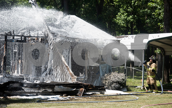 Smith County ESD2 fire fighter Carlos Sanchez uses the hose as he works to put out a structure fire in the 16,000 block of Big Oak Bay Road in New Chapel Hill. No one was injured in the fire.  (Sarah A. Miller/Tyler Morning Telegraph)