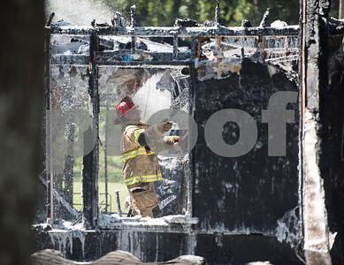 Smith County ESD2 fire fighter David Gerald works putting out a structure fire in the 16,000 block of Big Oak Bay Road in New Chapel Hill. No one was injured in the fire.  (Sarah A. Miller/Tyler Morning Telegraph)