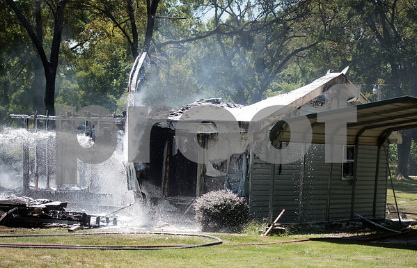 Smith County ESD2 fire fighters work to put out a structure fire in the 16,000 block of Big Oak Bay Road in New Chapel Hill. No one was injured in the fire.  (Sarah A. Miller/Tyler Morning Telegraph)