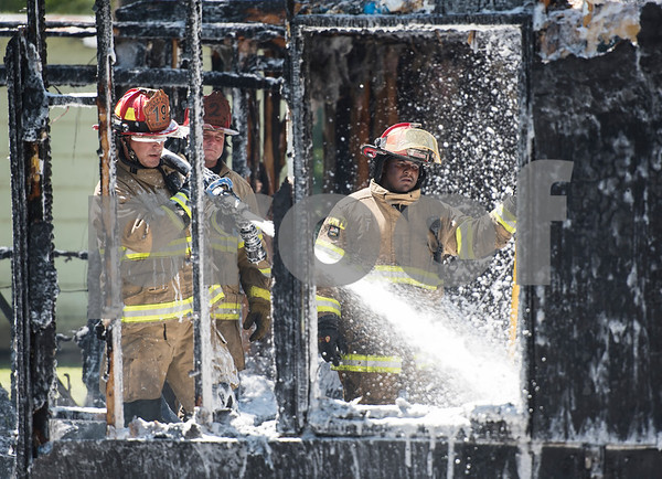 Smith County ESD2 fire fighters Adam Melson, David Gerald and Travis Johnson work putting out a structure fire in the 16,000 block of Big Oak Bay Road in New Chapel Hill. No one was injured in the fire.  (Sarah A. Miller/Tyler Morning Telegraph)