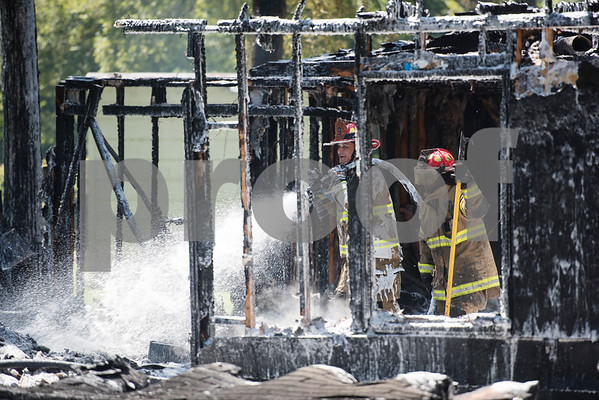 Smith County ESD2 fire fighters Adam Melson and Travis Johnson work putting out a structure fire in the 16,000 block of Big Oak Bay Road in New Chapel Hill. No one was injured in the fire.  (Sarah A. Miller/Tyler Morning Telegraph)