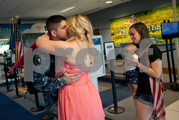 Manhatten Avina kisses her husband U.S. Navy Petty Officer 3 Daniel Avina as he arrives at the Tyler Pounds Regional Airport in Tyler, Texas Friday May 5, 2015. Avina  has been serving off the coasts of Iraq and Syria on the USS Carl Vinson for the past 10 months and had not yet met his son Ian Avina who has born four months ago while Avina was deployed. Avina grew up in Arizona and graduated from high school at Westview High School in Avondale. His wife has been staying in Tyler with her parents Kevin and Valerie Shepard while he has been serving in the Navy. They plan to return soon to Sam Diego where is stationed. Holding Ian is Manhatten's sister Shannon Shepard.  (photo by Sarah A. Miller/Tyler Morning Telegraph)