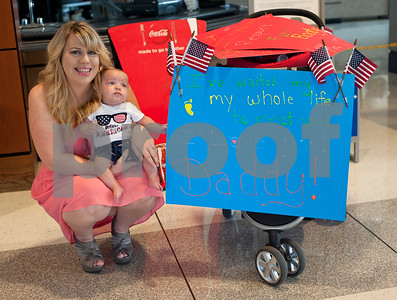 Manhatten Avina holds her son Ian as she waits for her husband's arrival in Tyler. U.S. Navy Petty Officer 3 Daniel Avina met his son Ian for the first time when he arrived at the Tyler Pounds Regional Airport in Tyler, Texas Friday May 5, 2015. Avina has been serving off the coasts of Iraq and Syria on the USS Carl Vinson for the past 10 months and had not yet met his son Ian Avina who has born four months ago while he was deployed. Avina grew up in Arizona and graduated from high school at Westview High School in Avondale. His wife Manhatten (not pictured) has been staying in Tyler with her parents Kevin and Valerie Shepard while he has been serving in the Navy. They plan to return soon to Sam Diego where is stationed.   (photo by Sarah A. Miller/Tyler Morning Telegraph)