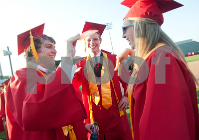 Robert E. Lee High School seniors Tucker Moore, James Davis and Courtney Merrell cool themselves by fanning their name cards as they wait for graduation to begin Friday night at Trinity Mother Frances Rose Stadium.   (photo by Sarah A. Miller/Tyler Morning Telegraph)