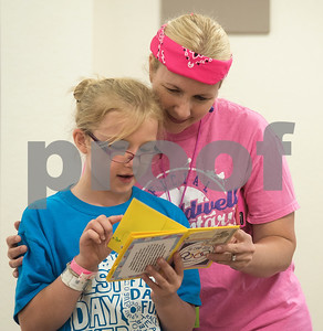 Camp leader Charlotte Allen of Tyler looks at her seven-year-old daughter Allie Allen journal she made during Girls in Action camp at Timberline Camp in Lindale Thursday June 9, 2016. Girls in Action and is a missions discipleship organization for girls in first through sixth grades.  (Sarah A. Miller/Tyler Morning Telegraph)