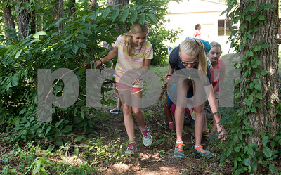 Alexis Meredith, 11, of Whitehouse and Kayla Stokes, 12, of Whitehouse, clean up an outdoor area as part of a mission project at Girls in Action camp at Timberline Camp in Lindale Thursday June 9, 2016. Girls in Action and is a missions discipleship organization for girls in first through sixth grades.  (Sarah A. Miller/Tyler Morning Telegraph)