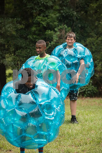 Texas Asthma Camp campers Omarian Frazier, 13, of Forney, Taje Thomas, 13, of Tyler, and Chevy Boole, 14, of Longview, play volleyball while wearing bubble suits and being sprayed with water by a hose during the week long camp held at Tyler Outdoor School. Texas Asthma Camp is in its 33rd year. The summer camp is for students who have an asthma diagnosis and a doctor is on staff 24/7 at the camp.    (Sarah A. Miller/Tyler Morning Telegraph)