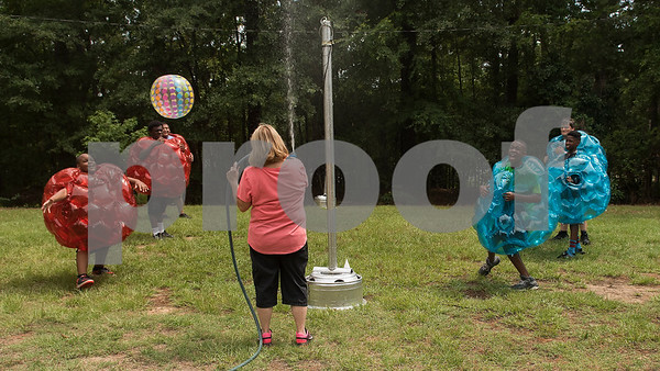 Marilyn Craig sprays water from a hose to cool down campers as they play volleyball while wearing bubble suits during Texas Asthma Camp at Tyler Outdoor School on Tuesday July 10, 2018. Pictured from left: campers Jaden Adams, 13, of Tyler, Devynn Hare, 14, of Dallas, camp counselor Ricky Santos, Taje Thomas, 13, of Tyler, Omarian Frazier, 13, of Forney and Chevy Boole, 14, of Longview. Texas Asthma Camp is in its 33rd year. The summer camp is for students who have an asthma diagnosis and a doctor is on staff 24/7 at the camp.    (Sarah A. Miller/Tyler Morning Telegraph)