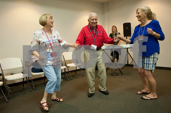 Participant Joe McAllister, center, dances with volunteers Carole Roberts, left, and Joanie Collier, right, during the Wonderful Wednesdays Day Club at Shiloh Road Church of Christ in Tyler Wednesday July 1, 2015. The program is part of the Alzheimer's Alliance of Smith County and provides social and cognitive stimulation as well as lunch for people with Alzheimer's disease or dementia.   (photo by Sarah A. Miller/Tyler Morning Telegraph)