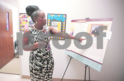 photo by Sarah A. Miller/Tyler Morning Telegraph  Family Self Sufficiency Home Ownership Coordinator Karesa Cooper points to the Family Self Sufficiency Spotlight of Success board inside of the City of Tyler Neighborhood Services office Thursday. The program helps adults make and obtain life goals such as becoming a home owner.