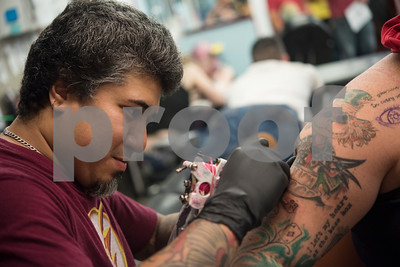 Marcelo Rosales makes a small key tattoo on Brittany Boss's tattoo sleeve as a Friday the 13th special at The Lost Boys Tattoo Shop in Tyler on Friday July 13, 2018. She also got a tattoo of an eye, sketched in at top left. It's an unofficial tradition at many tattoo parlors to offer specials on specific horror-themed or small tattoos on Friday the 13th. Some of the tattoo designs include the number 13. The Lost Boys Tattoo Shop had more than 50 tattoos to choose from, each costing $13 plus a $7 suggested tip.   (Sarah A. Miller/Tyler Morning Telegraph)