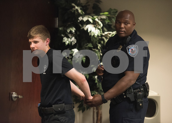 Tyler Police Department Community Response Officer Shane Jasper instructs students on proper handcuffing procedures with Judah Wilson, 16, of Bullard, during the Tyler Police Department's Explorer Post No. 310 meeting June 28, 2017. The program meets every Tuesday and allows students to explore careers in law enforcement.  (Sarah A. Miller/Tyler Morning Telegraph)