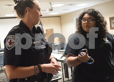 Tyler police officer Kerri Long teaches Pricila Gutierrez of Tyler, 18, about proper handcuffing procedure during the Tyler Police Department's Explorer Post No. 310 meeting June 28, 2017. The program meets every Tuesday and allows students to explore careers in law enforcement.  (Sarah A. Miller/Tyler Morning Telegraph)