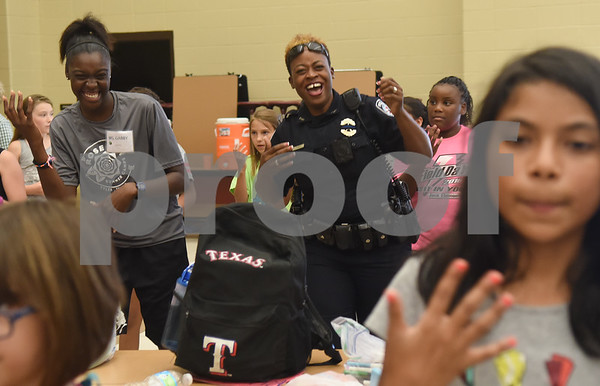 Tyler Police Department officer Tish Powell dances with children before lunch at the Rose City Summer Camps Public Safety Appreciation Day at Dixie Elementary School Wednesday July 20, 2016.  (Sarah A. Miller/Tyler Morning Telegraph)