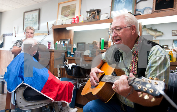 photo by Sarah A. Miller/Tyler Morning Telegraph  Tyler barber Cliff Lasseter, 69, plays the guitar as he sings an original song as his wife Becky Lasseter, 58, cuts a customer's hair (at left) Wednesday July 7th, 2013 at Cliff's Precision Kuts in Tyler. Lasseter has been a licensed barber since 1962  and opened Cliff's Precision Kuts in 1968.  At age 21 Cliff Lasseter took up guitar as a hobby, but says he didn't play seriously until age 62. Sometimes his customers come in and play or sing too.