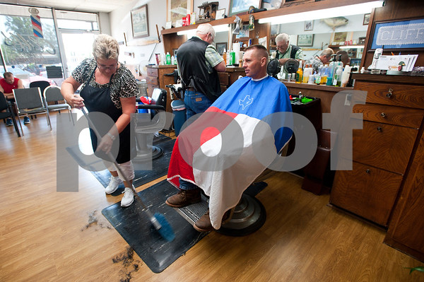 photo by Sarah A. Miller/Tyler Morning Telegraph  Tyler resident Becky Lasseter, 58, sweeps the floor as her husband Cliff Lasseter, 69, prepares to cut Bulard resident Sam Bercher's, 51, hair Wednesday July 7th, 2013 at Cliff's Precision Kuts in Tyler.
