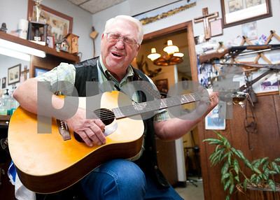 photo by Sarah A. Miller/Tyler Morning Telegraph  Tyler barber Cliff Lasseter, 69, plays the guitar as he sings an original song during a lull in business Wednesday July 7th, 2013 at Cliff's Precision Kuts in Tyler. Lasseter has been a licensed barber since 1962  and opened Cliff's Precision Kuts in 1968. He works at his shop with his wife of 26 years, Becky Lasseter, 58. At age 21 Cliff Lasseter took up guitar as a hobby, but says he didn't play seriously until age 62. Sometimes his customers come in and play or sing too.