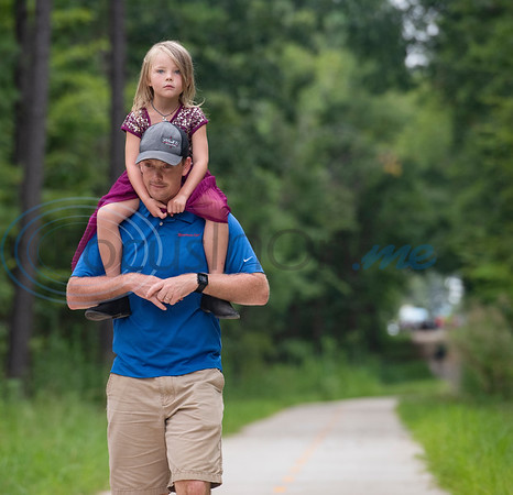 Sam Ivy of Tyler carries his daughter Dahlia Ivy, 4, on his shoulders as he walks the Legacy Trails during the grand opening event for Legacy Trails in Tyler. The new paved trail offers space for bicyclists, hikers and walkers to exercise between Tyler and Gresham.   (Sarah A. Miller/Tyler Morning Telegraph)